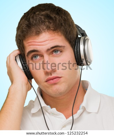 Young Man Listening to Music With Headphones against a blue background - stock photo