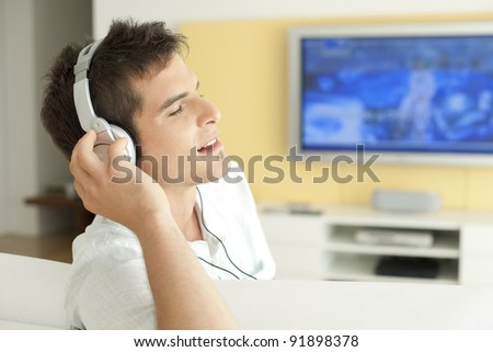 Young man listening to music with headphones at home. - stock photo