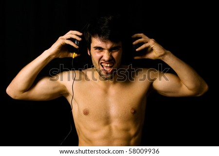 Young Man listening to music with headphones, on black background
