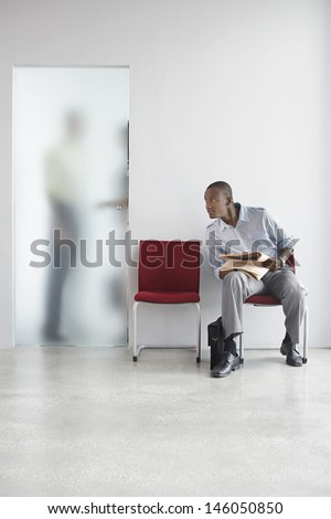 Young man listening to two people talk behind translucent door in office - stock photo