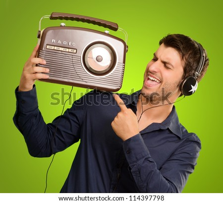 Young Man Listening To Vintage Radio On Green Background - stock photo