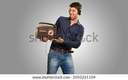 Young Man Listening To Vintage Radio On Grey Background