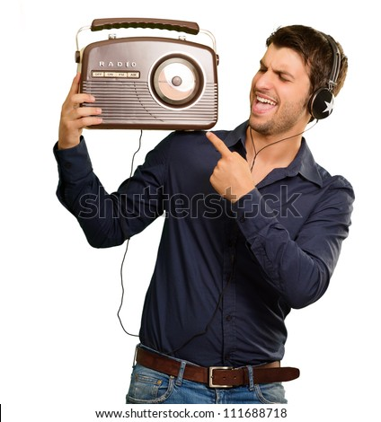Young Man Listening To Vintage Radio On White Background - stock photo