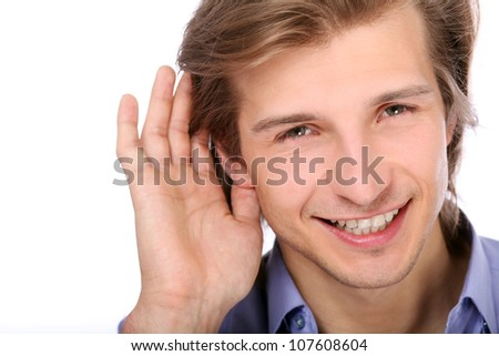 Young man listening with hand on ear over white background - stock photo