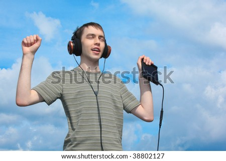 young man listens music in headphones outdoor - stock photo