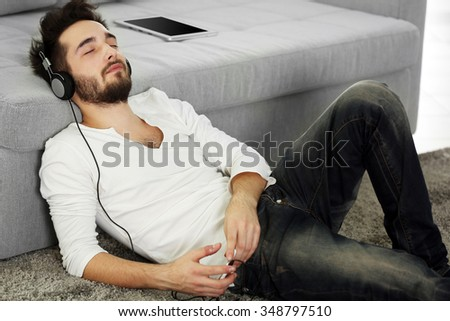 Young man listens music with headphones on the floor against grey sofa in the room
