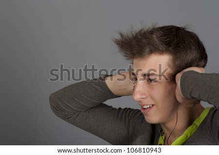 Young man listens to music with the music player through headphones
