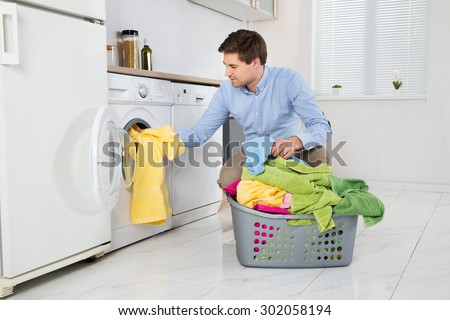 Young Man Loading Clothes Into Washing Machine In Kitchen - stock photo