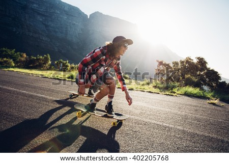 Young man longboarding outdoors on countryside road. Male skateboarding on a sunny day. - stock photo