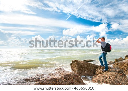 Young man look out to view standing on rock of windy sea on blue cloudy sky background. Summertime colorful horizontal image.