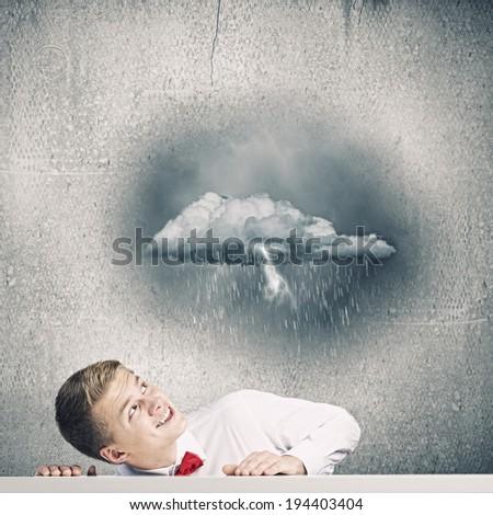 Young man looking above at raining cloud - stock photo