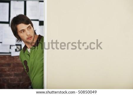 Young Man Looking Around Corner. - stock photo