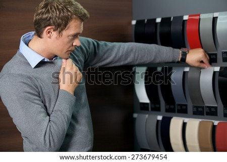 Young man looking at color swatch - stock photo