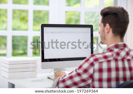 Young man looking at computer screen - stock photo