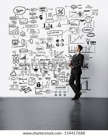 young man looking at drawing business concept on wall - stock photo