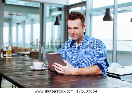 Young man looking at his tablet - stock photo