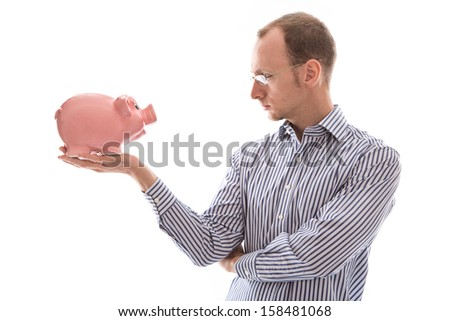 Young man looking at pink piggy bank - isolated on white background - stock photo