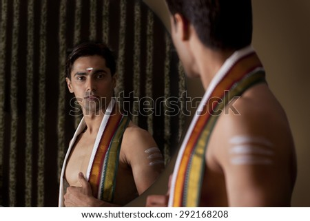 Young man looking at self in mirror - stock photo