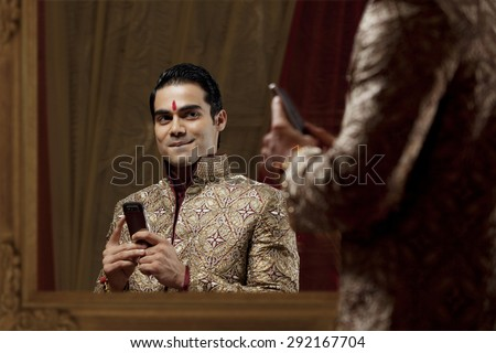 Young man looking at self in mirror and smiling while holding mobile phone - stock photo