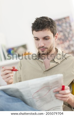 young man looking at the classifieds in the newspaper - stock photo