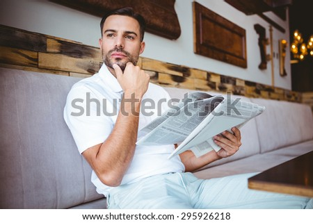 Young man looking away while holding a newspaper in a coffee shop