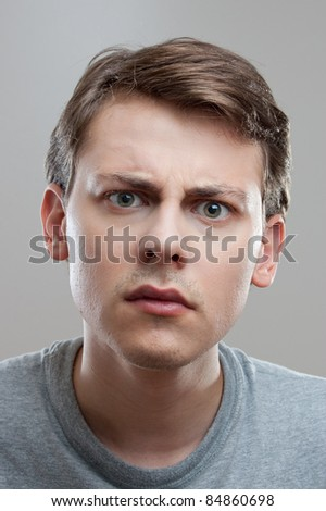 young man looking curious into camera - stock photo
