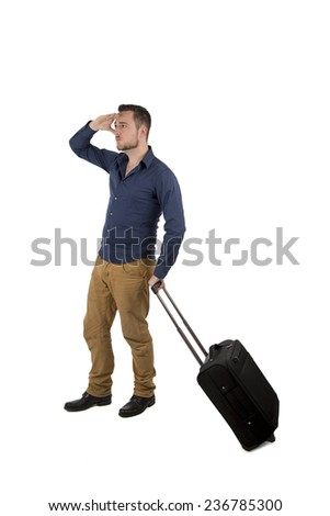 Young man looking far away while holding suitcase against a white background - stock photo