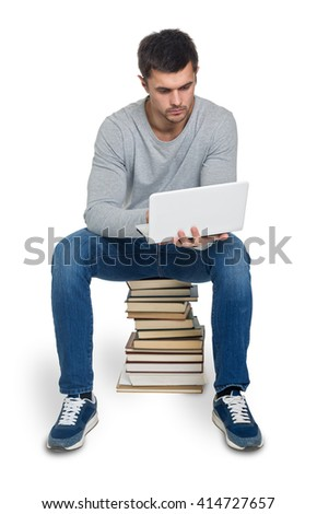 Young man looking for information in books and on the computer, isolated
