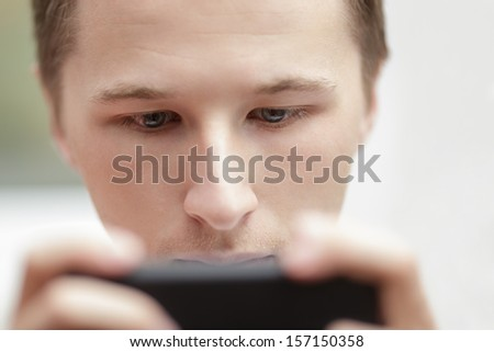 young man looking in the screen of mobile phone, close up portrait - stock photo