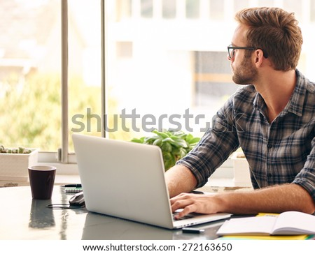 Young man looking out at the view from his home office with his morning cup of coffee, while working on his notebook - stock photo