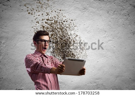 Young man looking shocked in tablet pc