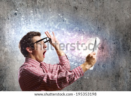 Young man looking shocked in tablet pc - stock photo