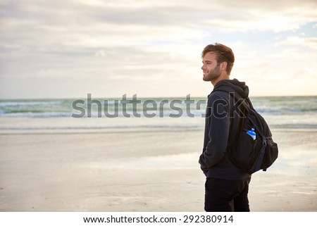 Young man looking thoughtful while standing alone on a beach in the morning wearing a hoodie and backpack - stock photo