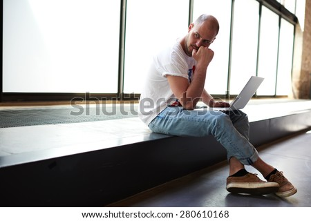 Young man looking thoughtful while working on laptop computer holding it on the knees, university student using notebook for write his coursework, freelancer sitting in modern interior thinking about  - stock photo