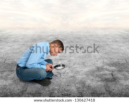 young man looking through a magnifying glass - stock photo