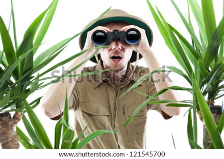 Young man looking through binoculars with an amazed expression, palm trees on foreground out of focus, isolated on white - stock photo