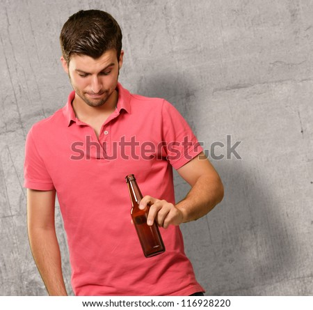 Young Man Looking Through Empty Bottle, Indoor - stock photo