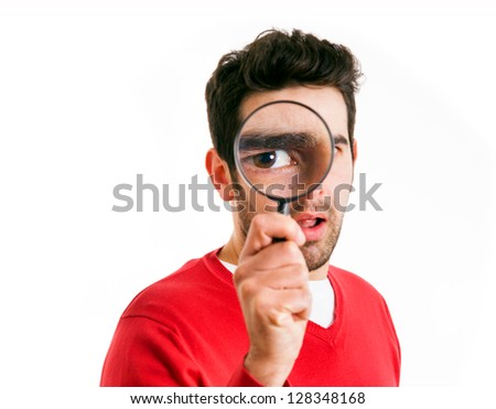 Young man looking through magnifying glass, isolated on white