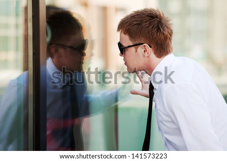 Young man looking through the window
