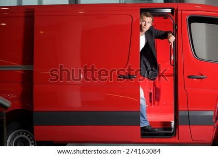 Young man looking through van door, portrait - stock photo
