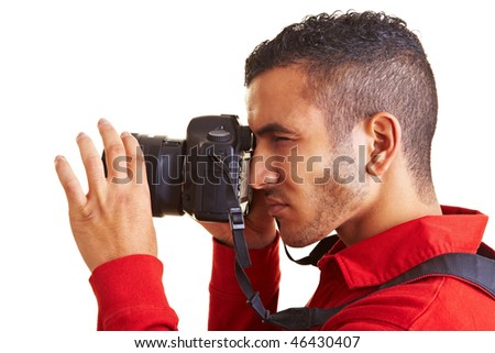 Young man looking through viewfinder of digital camera