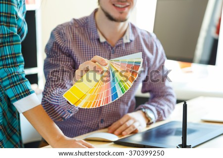 Young man looking to a color paint palette at home office - stock photo