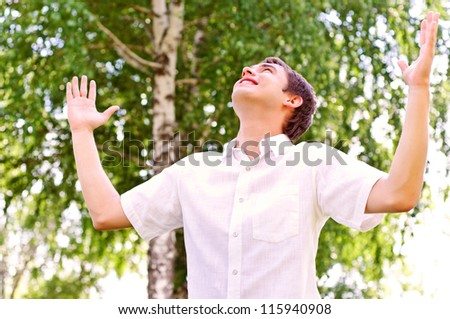 young man looking to the sky, holding his hands up, the expectation of success - stock photo