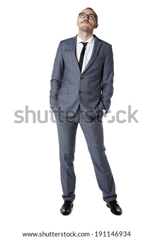 Young man looking up and wait for something. Hands in pockets. - stock photo