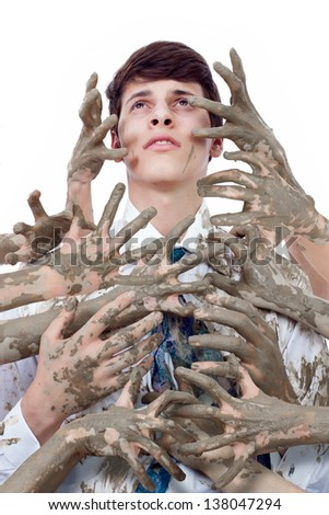 Young man looking up stained by multitude of dirty hands - stock photo