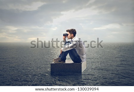 young man looking with binoculars - stock photo