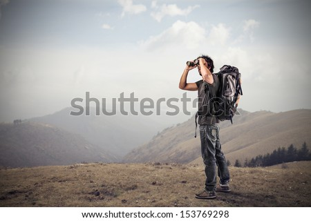 young man looking with binoculars in the mountains - stock photo