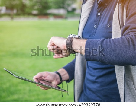 Young man looks at his watch and holding digital Tablet