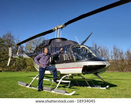 Young man looks at skies standing next to small private helicopter on grass in estate. Shot  near Cape Town, Western Cape, South Africa. - stock photo