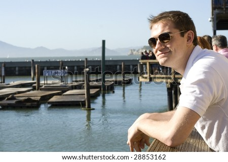 Young man looks out over the San Francisco Bay at the Pier.